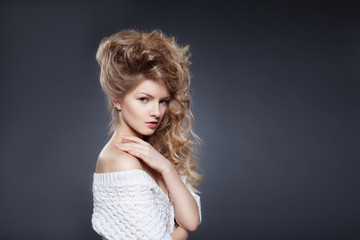 Portrait of beautiful female model with blond curly hair over gr