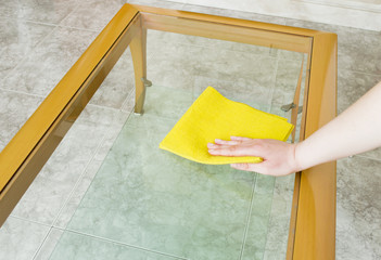 cleaning a glass table with yellow cloth