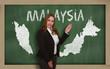 Teacher showing map of malaysia on blackboard