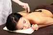 Beautiful young woman in spa salon with spa stones,