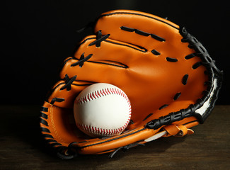 Baseball glove and ball on dark background