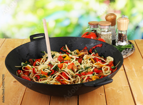 Noodles with vegetables on wok on nature background background