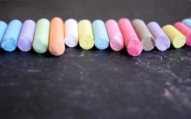 Fila di gessi colorati su lavagna nera