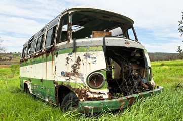 Abandoned old bus in a green field