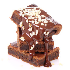 Slices of a brownie on white coverd with chocolate and nuts