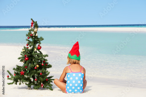 Girl Sitting On Beach With Christmas Tree And Hat