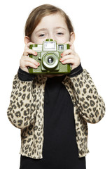 Young girl holding a camera smiling
