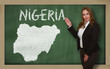 Teacher showing map of nigeria on blackboard