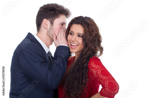 Man whispering a secret to a surprised young lady