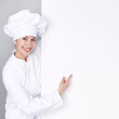 Female chef cook shows a blackboard with copyspace