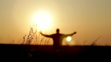 Silhouette of man on the sunrise. Freedom concept.