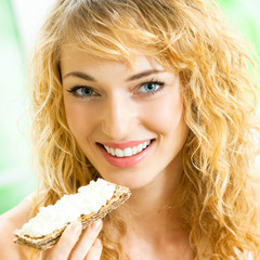 Portrait of young happy woman eating crispbread