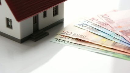 little house with house key and euro money