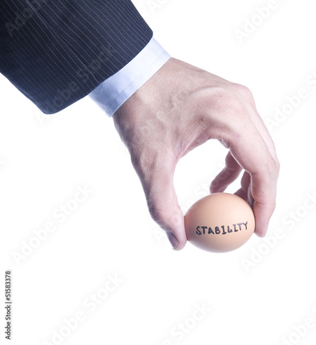 Egg with inscription Stability between fingers. Concept of the c