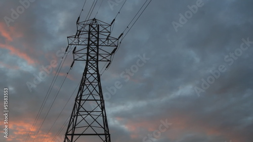 Electrical pylon. Sunset timelapse clouds.