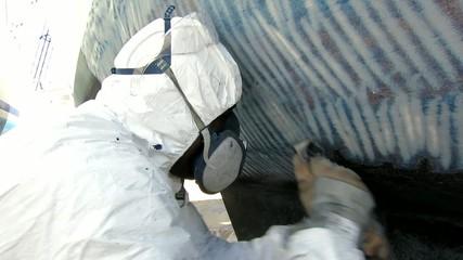 Antifouling - Grundierung eines Segelbootes - Mann arbeitet