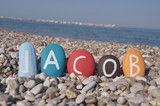 Jacob, male name on colourful stones over pebbles