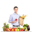 Smiling man holding an apple and bag with food products, posing