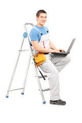 Full length portrait of a handy man with a laptop sitting on a l