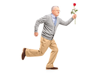 Full length portrait of a mature gentleman running with a red ro