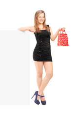 Full length portrait of a young female with a gift bag standing