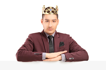 Handsome prince posing on a panel with a diamond crown