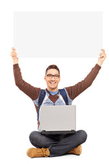 Smiling male student sitting with laptop and holding a blank pan