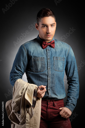 Attractive male model holding coat and posing
