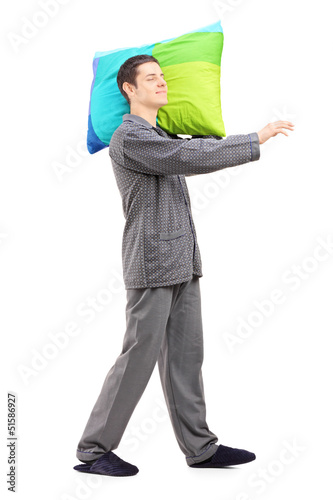 Full length portrait of a man sleepwalking and holding a pillow