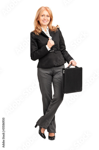 Full length portrait of a mature businesswoman leaning against a