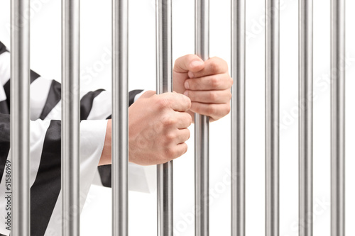 Male holding prison bars