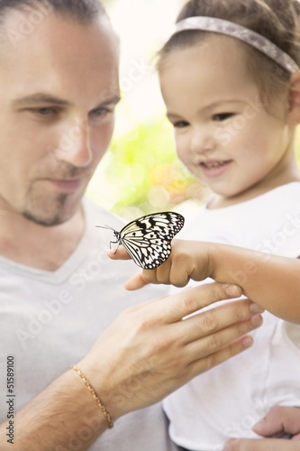 Dad and daughter are looking a butterfly
