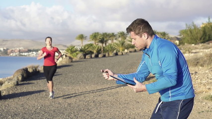 Female jogger with personal trainer, super slow motion