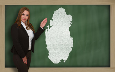 Teacher showing map of qatar on blackboard