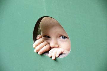 Kind späht durch ein Loch