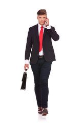 business man walks with brief & phone