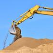 new yellow excavator working on sand dunes. Scoop close-up
