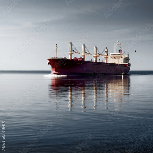 Leinwanddruck Bild cargo ship sailing in still water