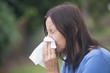 Woman suffering flu sneezing in tissue