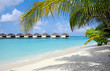 row of water villas on a tropical island