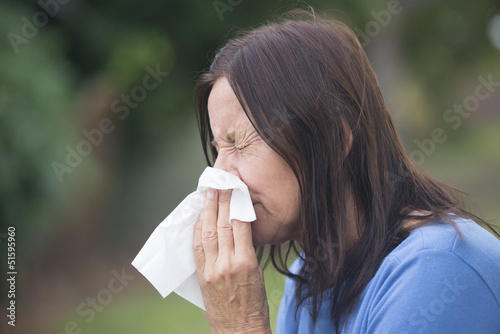 Woman suffering flu sneezing in tissue