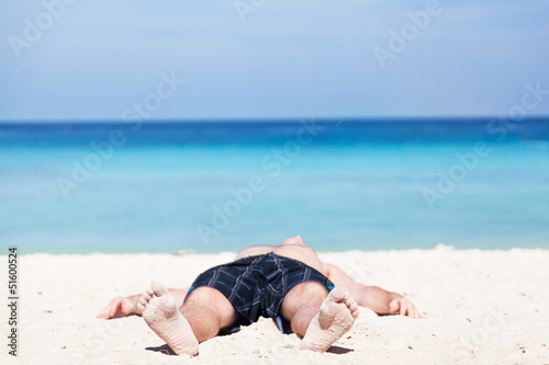 Man lies on a beach on an ocean coast