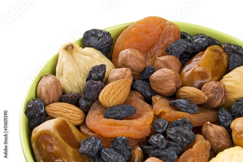 Dried fruits and nuts mixed in green bowl close up