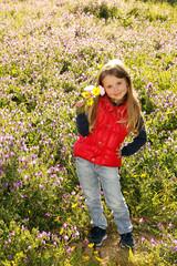 Bambina sorridente in giardino raccoglie i fiori
