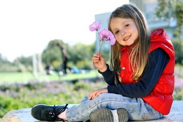 Bambina seduta su un masso di pietra con i fiori in mano