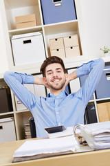Erfolgreicher Mann im Büro lehnt sich zurück