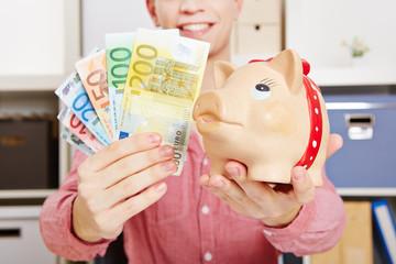 Hände halten Euro-Geldscheine und Sparschwein