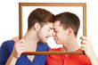 Schwules Paar hält Rahmen vor Gesicht
