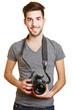 Junger Mann hält Kamera als Fotograf