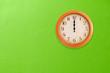 Leinwanddruck Bild - Clock showing 12 o'clock pm on a green wall